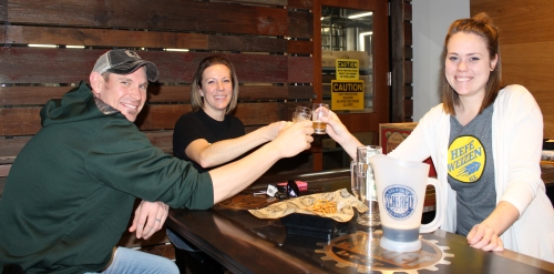 Schlafly Bottleworks Tasting Room. After a tour of the brewery Aaron Moore (Left), Jennifer Moore (Middle), and tour guide Sarah Rybicki (Right), taste a variety of beer brewed at Schlafly. Photo by Holly Shanks.