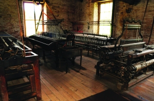 Watkins Woolen Mill State Historic Site. These extremely rare textile machines–two ring-framed ply twisters and a plain loom of 1860 vintage–demonstrate Watkins Woolen Mill's fame as America's finest preserved nineteenth-century textile factory. The mills has been designated a National Historic Landmark. Photo credit:Ron Ginther