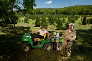 Domien and Eileen Meert at their Christmas tree farm near Festus, Mo. Domien holds the first tree dibble he ever used when he started his tree farm. Photo by MDC Staff, courtesy Missouri Department of Conservation.
